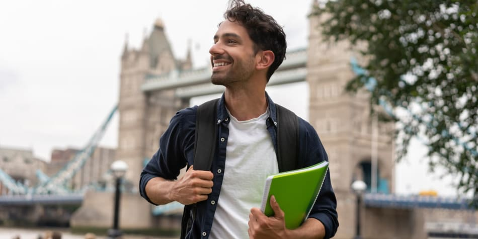 guy holding a book: Top 8 reasons to study abroad
